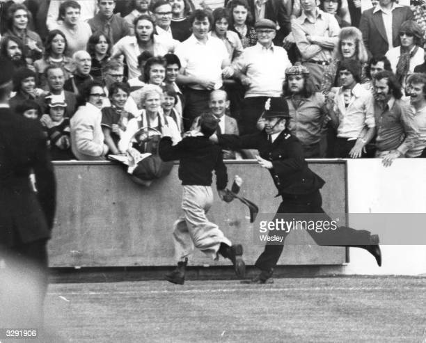 A Manchester United football fan invades the pitch and is chased by a policeman prior to the start of the first match of the season between Orient...