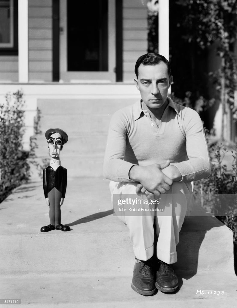 American silent screen comedian and actor Buster Keaton (1895-1966), known as 'The King of Deadpan' sits beside a model resembling himself.