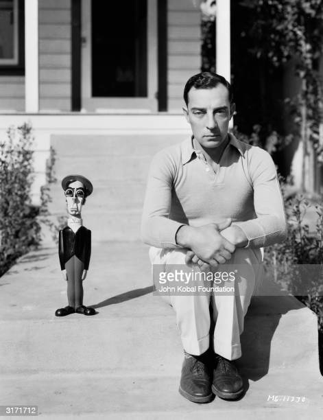 American silent screen comedian and actor Buster Keaton known as 'The King of Deadpan' sits beside a model resembling himself