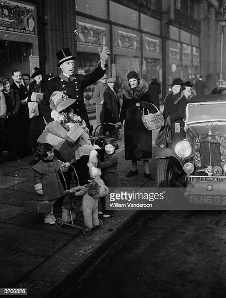 The store commissionaire hailing a taxi for two young shoppers outside Whiteley's Department Store in Bayswater, London.