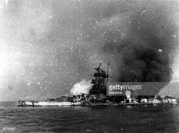 A broadside view of the scuttling of the German battleship 'Admiral Graf Spee' showing smoke and flames pouring from the German ship as explosions...