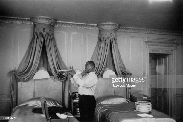 American jazz musician Louis Armstrong playig the trumpet inside his suite at the Dorchester Hotel in London. Original Publication: Picture Post -...