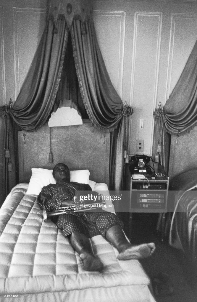 Louis 'Satchmo' ('Satchelmouth') Armstrong (1900 - 1971), the great jazz trumpeter and vocalist, relaxing in his suite at the Dorchester Hotel in London. Original Publication: Picture Post - 8771 - Blowin' For Hungary - pub. 1956