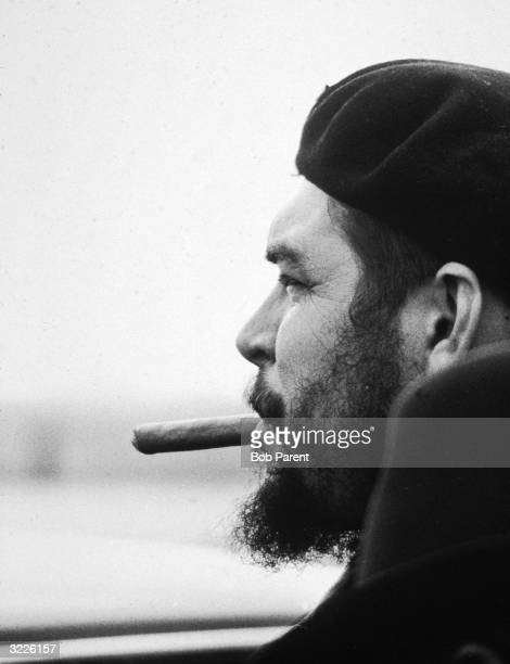 Profile portrait of Argentineborn Cuban Marxist revolutionary Ernesto 'Che' Guevara wearing a beret and smoking a cigar in an airport probably New...