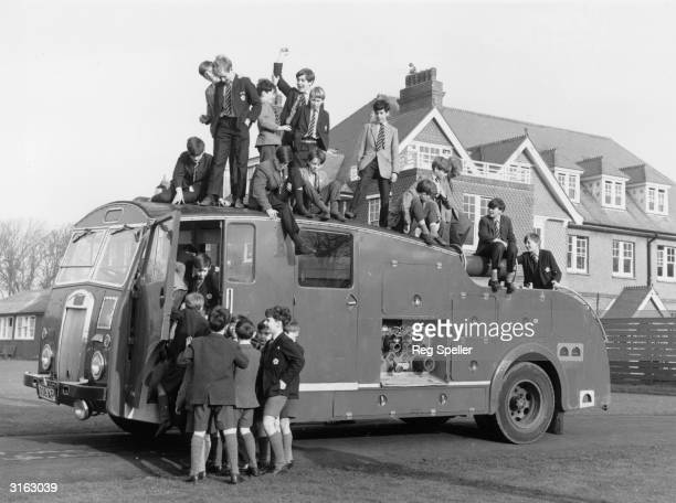 Pupils at St Peter's preparatory school at Seaford in Sussex climb on a redundant London fire engine which was bought for their school at auction for...