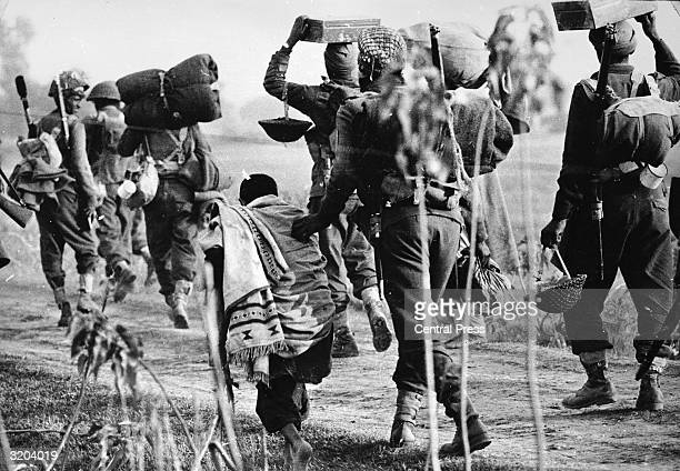 An elderly Pakistani refugee is pushed aside by Indian troops advancing into the East Pakistan area during the Indo-Pakistani war.