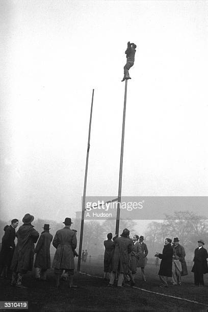 Guy's Hospital supporter hanging his team's colours on top of the goal post, before the start of their rugby match against St. Bartholomew's Hospital...