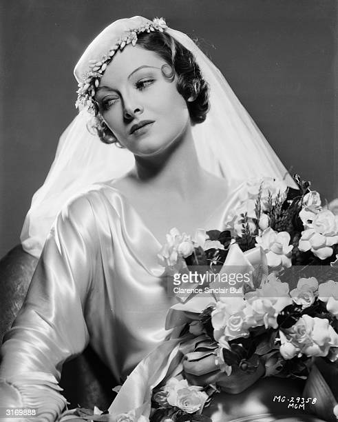 American actress Myrna Loy dressed as a bride and carrying a bouquet of flowers