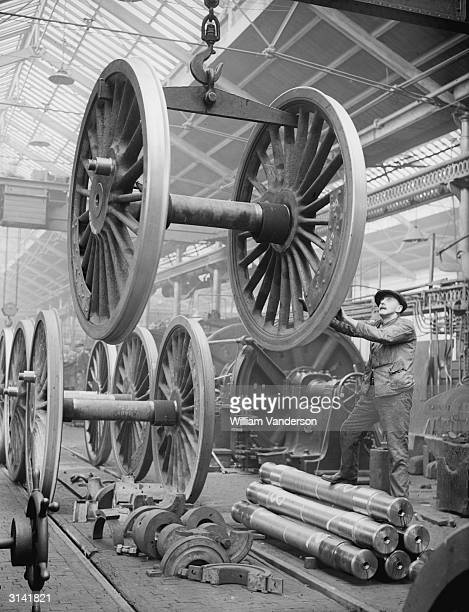 A workman lowering a set of locomotive's wheels at a locomotive works in Crewe