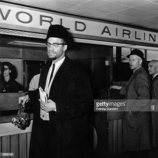 Black Muslim activist Malcolm X arrives at London Airport carrying a portable cinecamera