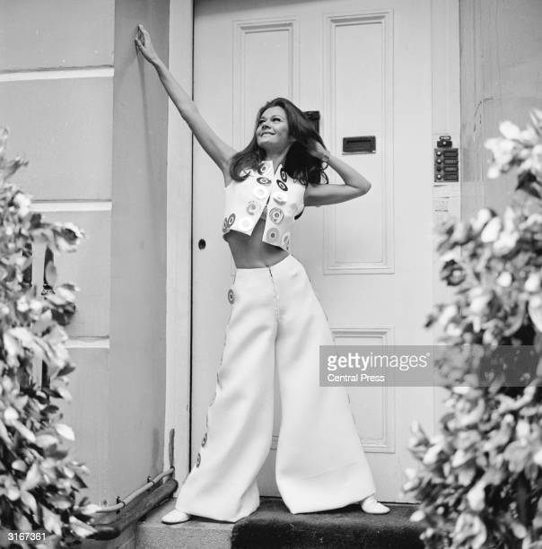 British actress Imogen Hassall wearing white culottes and a mini bolero trimmed with silver and purple paillettes by designer Tsarina