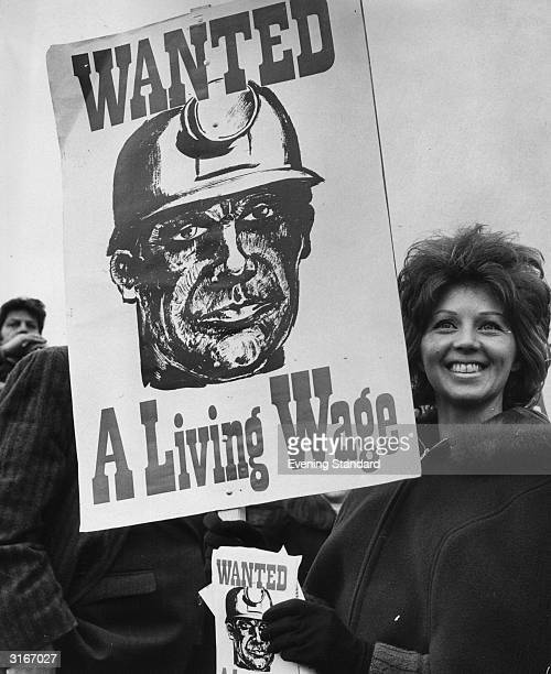 Margaret Dobb the wife of a Nottinghamshire miner holds up a placard reading 'Wanted A Living Wage' at a strike meeting at Tower Hill in London