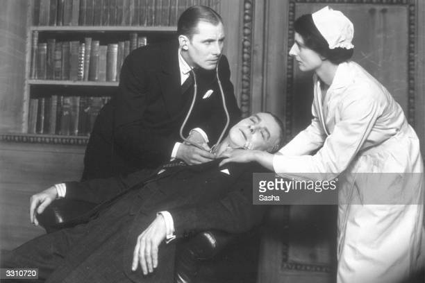 A doctor and nurse tend to a man who has collapsed in a scene from the play 'Dinner at Eight' at the Palace Theatre London