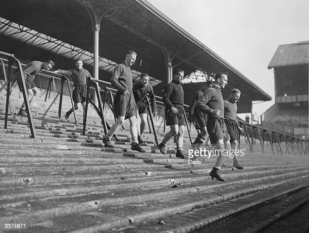 Tottenham Hotspur FC soccer team in training running up and down the terrace at White Hart Lane London Left to right Hall Gibbons Ward Page Hitchins...
