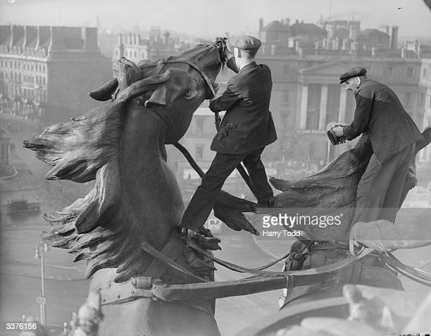 Workmen cleaning the immense statue of two horses pulling a quadriga or chariot atop the Wellington Arch on Hyde Park Corner London