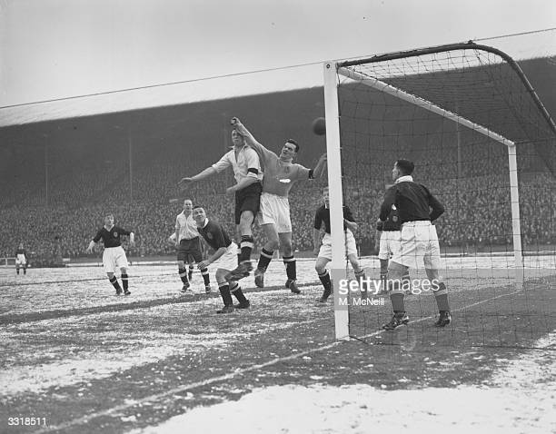 England centreforward Tommy Lawton heads the ball past Scotland's goalkeeper Dawson to score for England during an international match at Wembley...