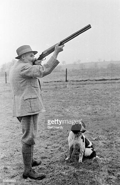 Trainer takes aim at a pheasant while his gun dog sits calmly by his side. Original Publication: Picture Post - 4480 - Training Gun Dogs - pub. 1948