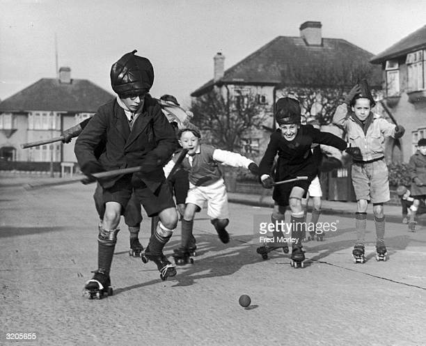 A group of boys playing hockey on rollerskates in Chessington Avenue Bexleyheath They are wearing teacosies as protective headgear and have newspaper...