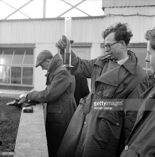 A Picture Post tester examining a sample of new 80 octane plus petrol at Goodwood race track Original Publication Picture Post 6349 We Try The New...