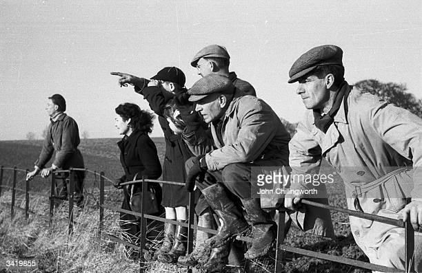 Followers of the Pytchley Hunt watching a fox escape from the hounds. Original Publication: Picture Post - 6531 - A Hunting We Will Go - pub. 1953