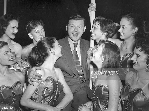 British comedian Benny Hill poses with a group of showgirls