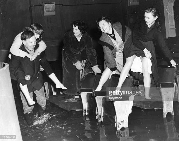 Members of the cast of 'The Cat And Canary' make their way along seats to stay off the flooded floor of the theatre while one woman gets a piggy back...