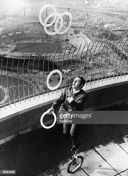 World famous juggler Rudy Horn of the Munich Circus Krone rides a unicycle and juggles with Olympic rings at the top of the TV Tower high above the...
