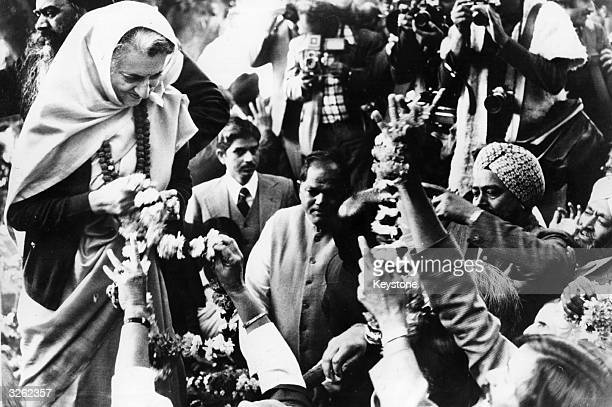 Indira Gandhi receives garlands of flowers from well wishers after resuming premiership of India