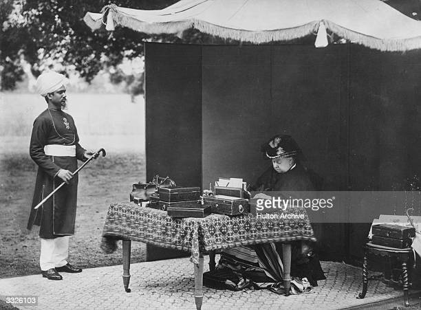 Under a canopy Queen Victoria writes letters at a table piled with despatch boxes Her Indian servant stands holding her walking stick and waiting for...