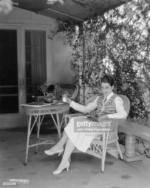 Canadian actress Norma Shearer sits on a wicker chair on a shady verandah, reading a book.