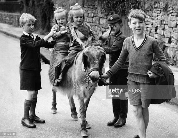 Four young evacuees from London and the South East coast enjoy rides on a donkey belonging to a local boy in the West Country