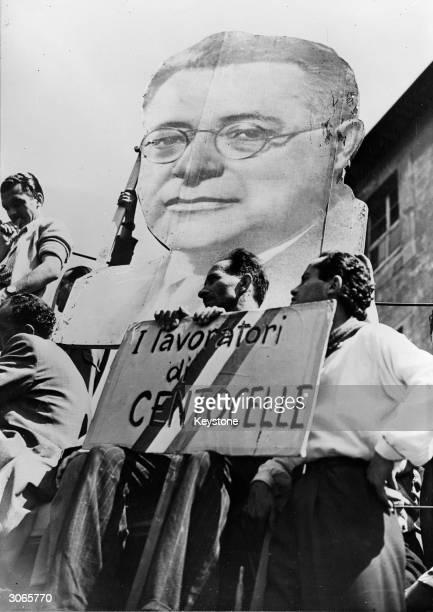 A massive portrait of Italian Communist leader Palmiro Togliatti at a Communist meeting in the Grand Comizio The sign beneath reads 'Lavoratori di...