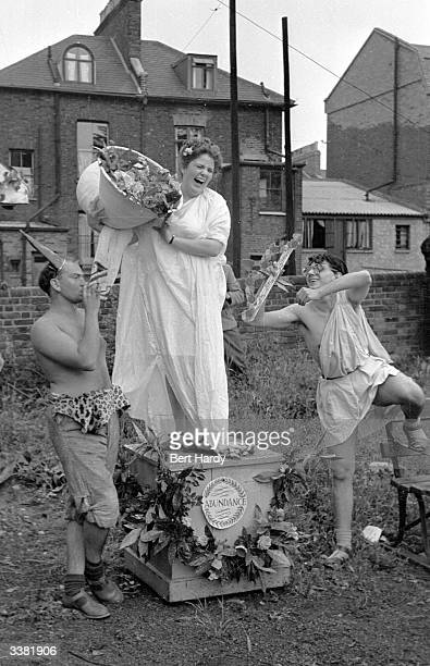 A trio of students at the Goldsmith's Art College end of term party in London set up a classical tableau depicting the goddess Fortuna with a horn of...