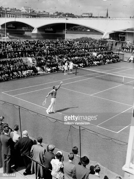 British tennis player and former Wimbledon champion Fred Perry demonstrates his serve during an exhibition match on London's South Bank tennis courts...