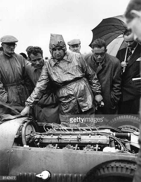 A Maserati engineer and onlookers examine the engine of a Maserati at Silverstone