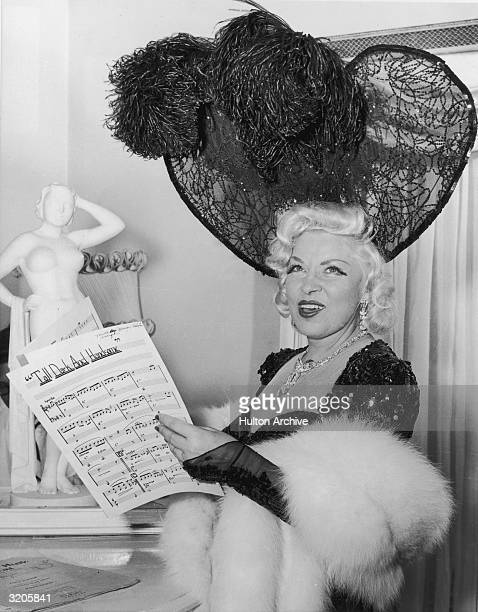 American actor Mae West smiles while holding the sheet music for 'Tall, Dark and Handsome,' a song she performed during her nightclub engagement in...