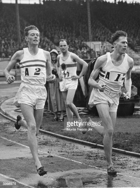 Roger Bannister receiving the baton from B Shewson during the 4 x 1500 metre relay race at the International Athletics meeting between England and...
