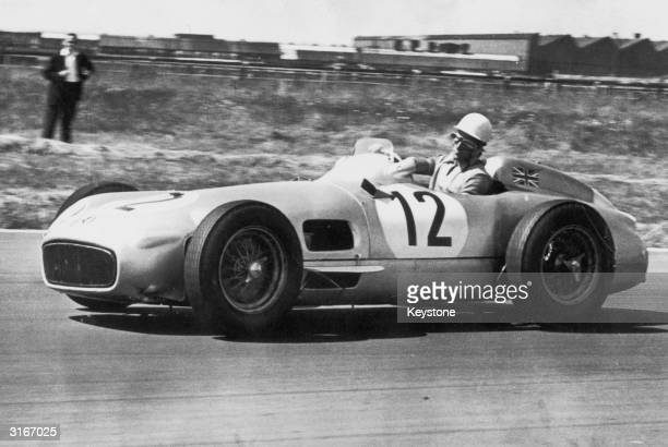 English motorracing driver Stirling Moss in a Mercedes at Cottage Corner on the Aintree circuit in Liverpool during the British Grand Prix Moss won...