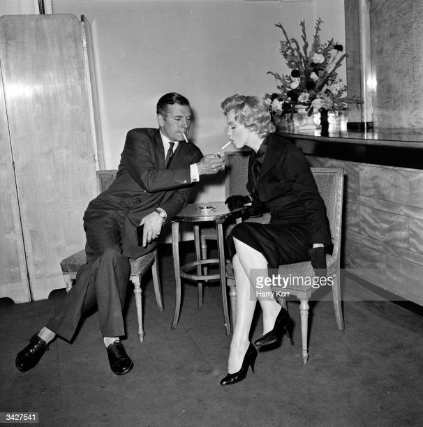 American film star Marilyn Monroe accepts a light from British thespian Laurence Olivier at a press conference at the Savoy Hotel London