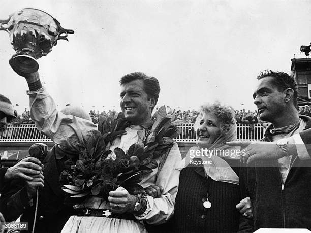 Wolfgang von Trips driver of the winning Ferrari holds high his trophy after the British Grand Prix at Aintree Liverpool On the right is Phil Hill...