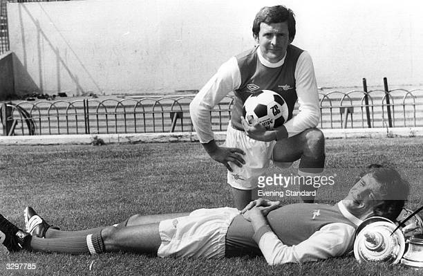 Arsenal Footballers John Hollins and David O'Leary at Highbury O'Leary appears to be using the FA Cup as a headrest