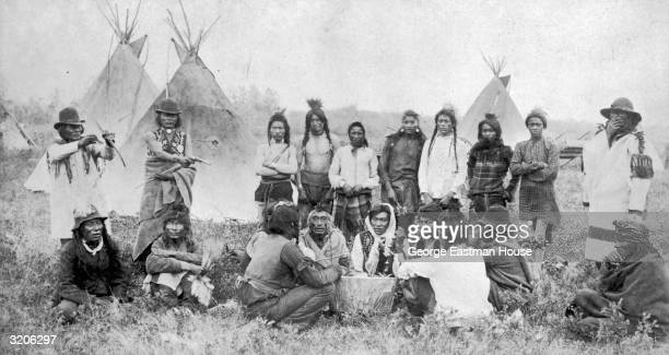 Fulllength image of a Native North American pow wow at Moosomin North West Territories Canada Several men beat on a drum while others some of them...