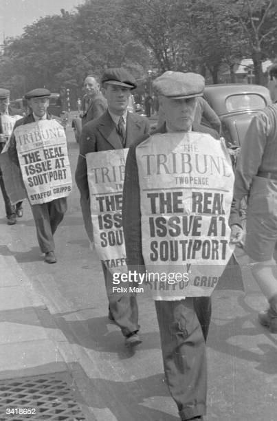 Demonstrators wearing banners advertising the Tribune newspaper displaying a headline concerning the possible expulsion of senior politician Stafford...
