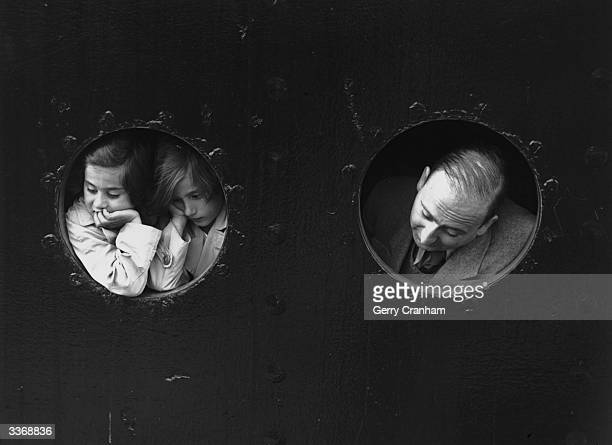 German Jewish refugees looking through portholes aboard the HamburgAmerika liner 'St Louis' on arrival at Antwerp where a temporary home was found...