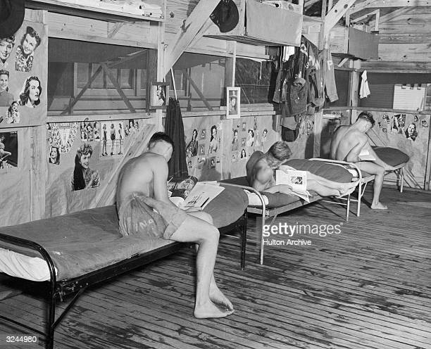 Three German POWs wearing only shorts relaxing with books and magazines on cots in one of the prisoners' barracks at Camp Blanding Florida during...