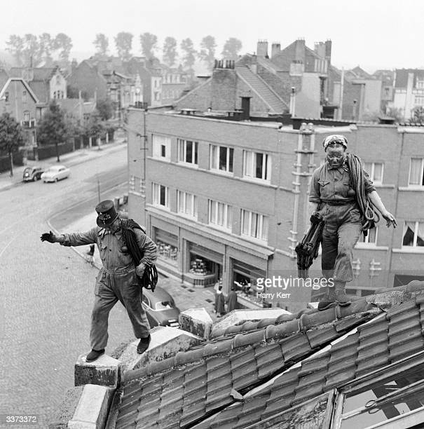 Mr Antoine Behiels of WoluweStPierre Brussels and his wife Marie walk along roof tops as they sweep chimneys 'I've fallen more than once' says...