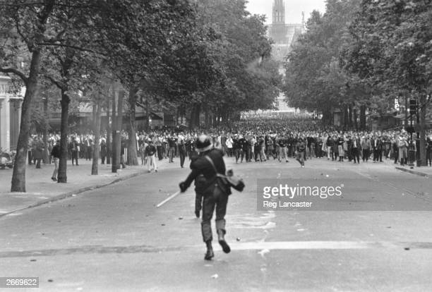A policeman throws a tear gas canister to disperse crowds during student riots in Paris