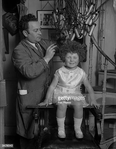 Hairdresser M Balbus removes the electric curlers from little Peggy Vaff's hair after giving her a bubble perm