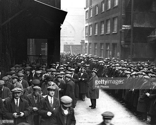 Huge crowd of labourers gathers at the London docks in the hopes of getting some work.