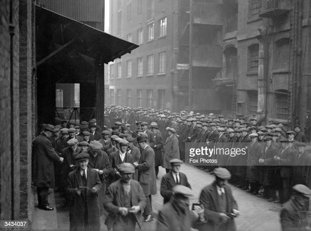Unemployed labourers waiting for work at a dockyard